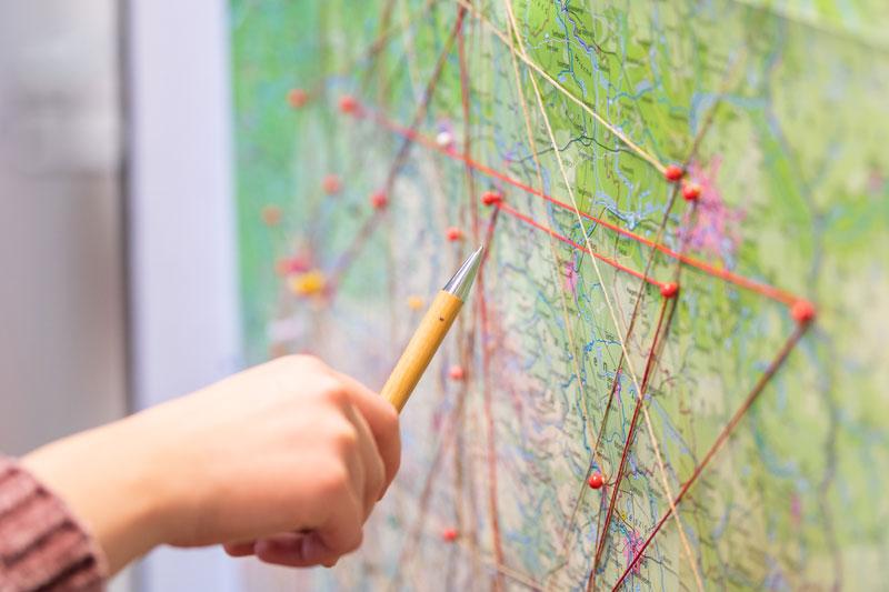 Person zeigt mit Stift auf Weltkarte. Situation im Workshop